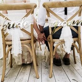 Prachtige goudkleurige stoeldecoraties Bride en Groom